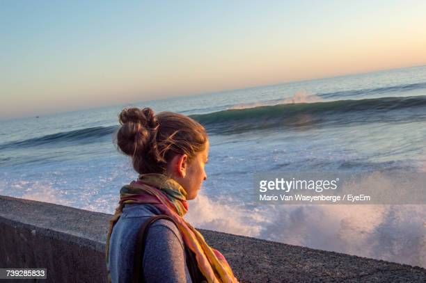 Side View Of Woman Looking At Waves Splashing In Sea During Sunset