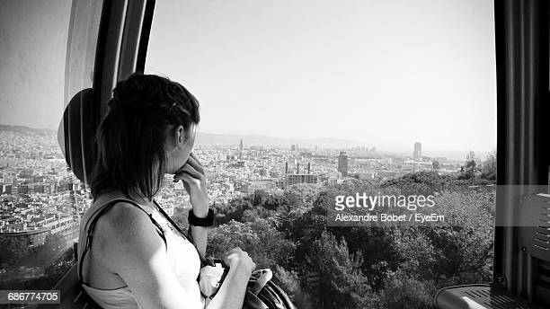 Side View Of Woman Looking Through Window In Overhead Cable Car