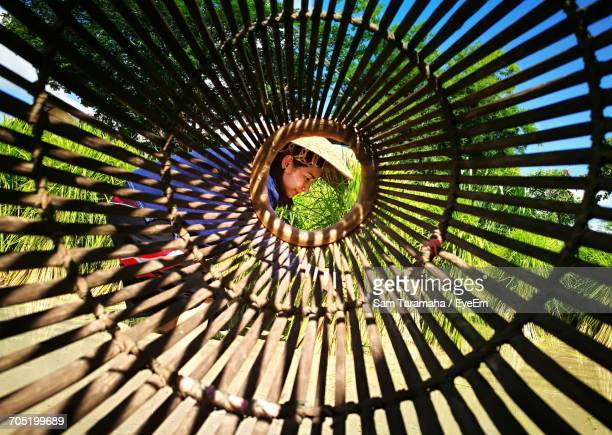 Side View Of Woman On Field Seen Through Wooden Fish Coop At Farm