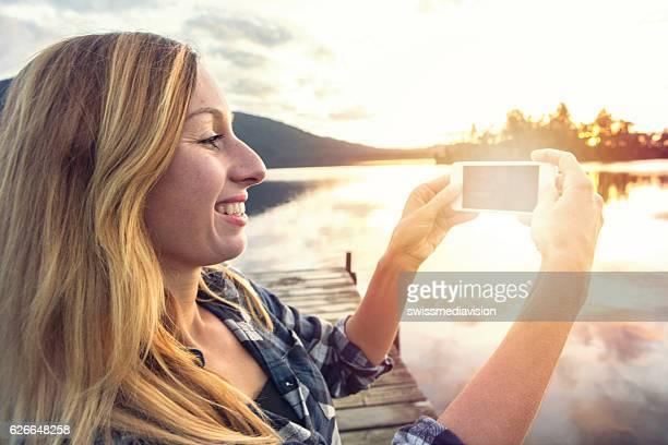 Side View Of Woman Photographing Lake Through Smart Phone
