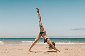 side view of woman practicing downward facing dog yoga pose on sandy beach