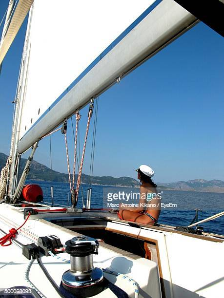Side view of woman relaxing on sailboat