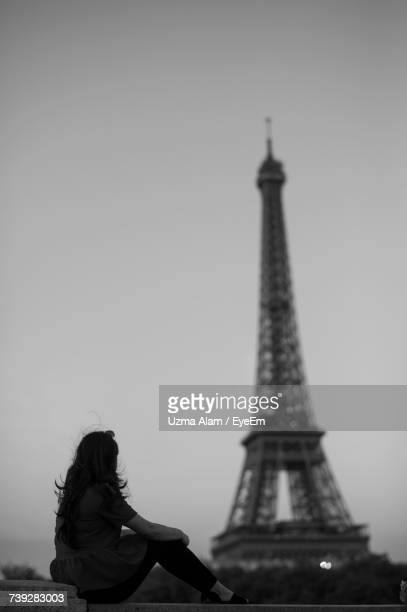 Side View Of Woman Sitting On Retaining Wall Against Eiffel Tower