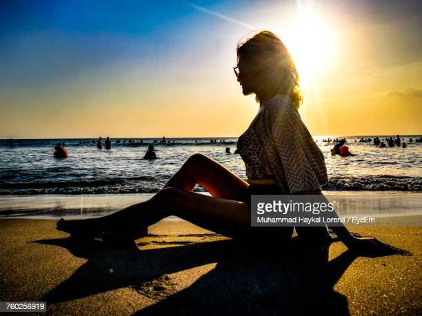 Side View Of Woman Sitting On Shore At Beach During Sunset