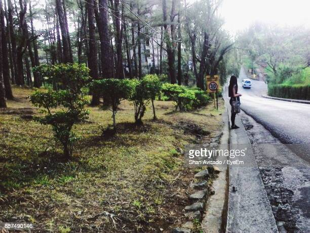 Side View Of Woman Standing By Road