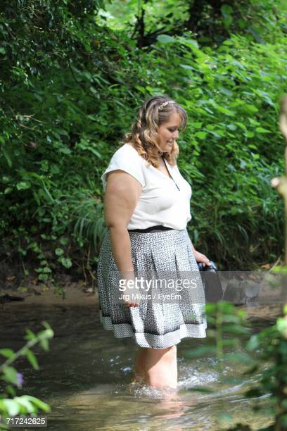 Side View Of Woman Standing In River Against Plants