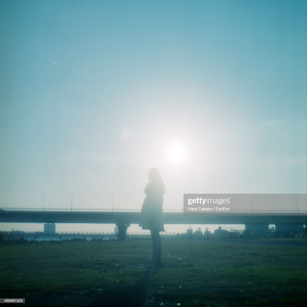 Side View Of Woman Standing On Grassy Field Against Clear Sky : Stock Photo
