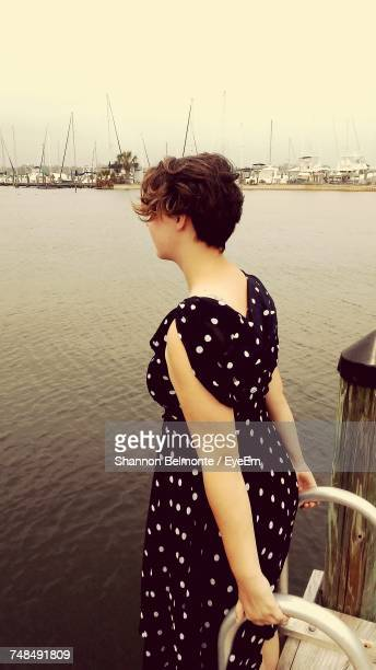 Side View Of Woman Standing On Jetty By River