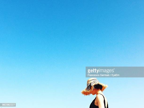 Side View Of Woman Standing Outdoors Against Clear Blue Sky