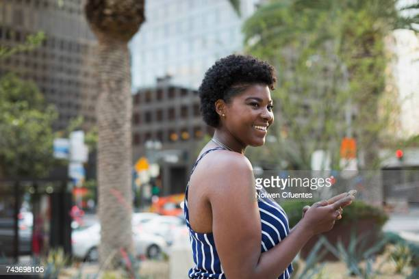 Side view of woman using mobile phone against buildings in city, Los Angeles, California, USA