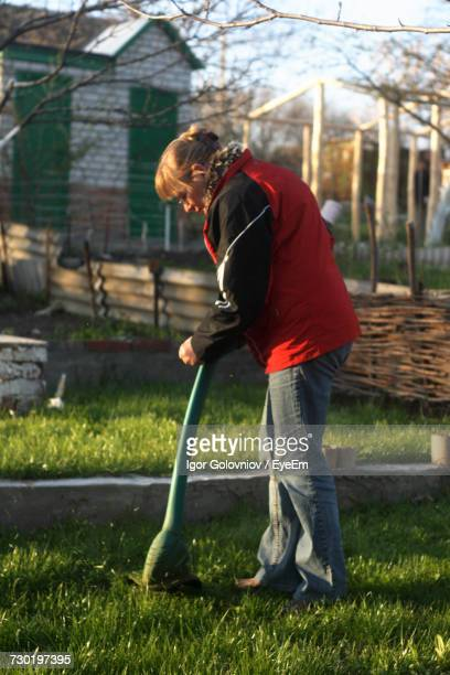 Side View Of Woman Using Weed Trimmer In Yard