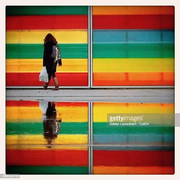 Side view of woman walking along colorful wall with reflection on street