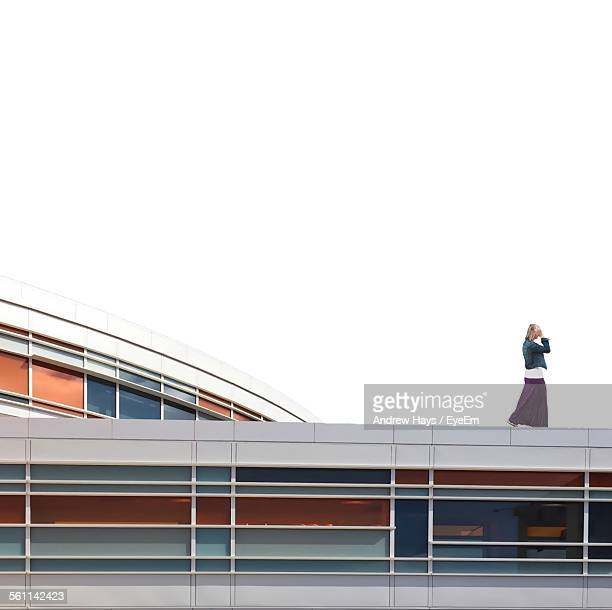 Side View Of Woman Walking On Top Of Building