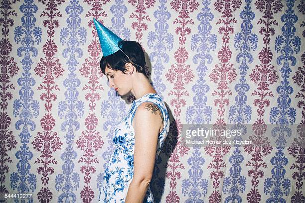 Side View Of Woman Wearing Cap While Standing Against Patterned Wall