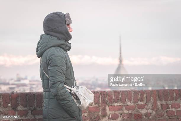 Side View Of Woman Wearing Winter Coat While Standing By Retaining Wall