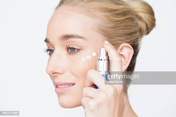 Side view of woman with hair bun applying face cream to cheek