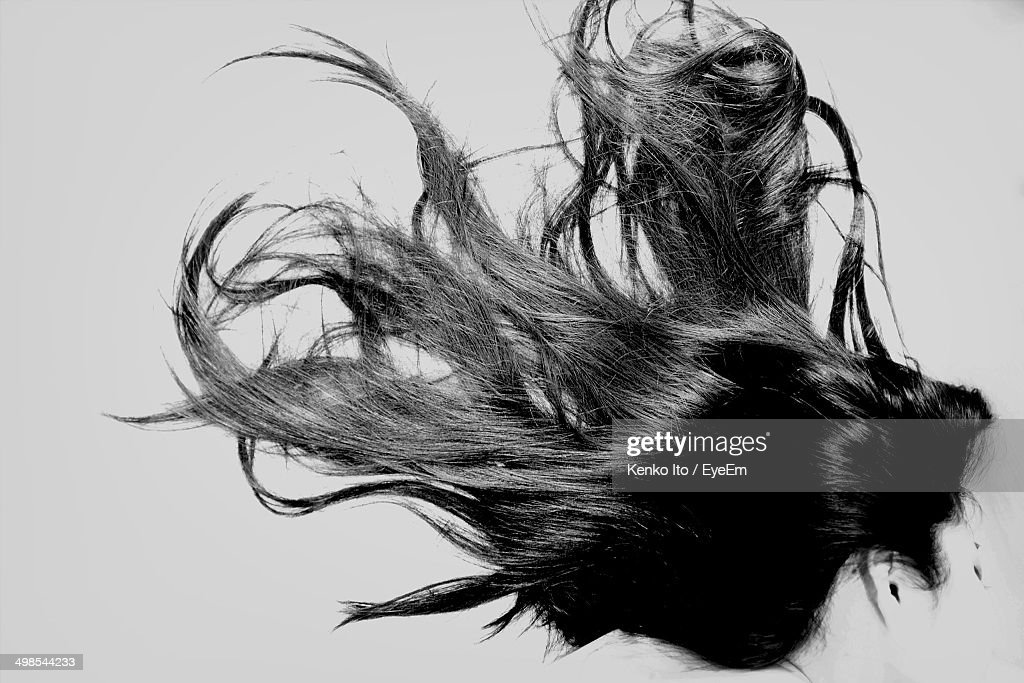 Side view of woman with long black hair over white background