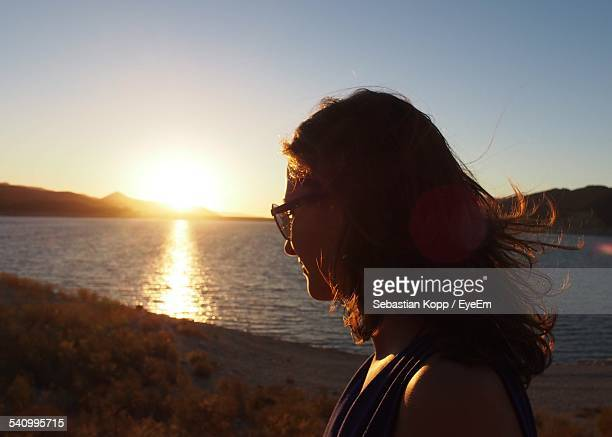 Side View Of Woman With Sunglasses By Lake During Sunset