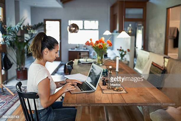 Side view of woman working on laptop at dining table