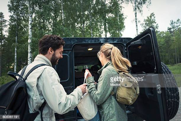 Side view of wonderlust couple unloading bag from jeep at countryside