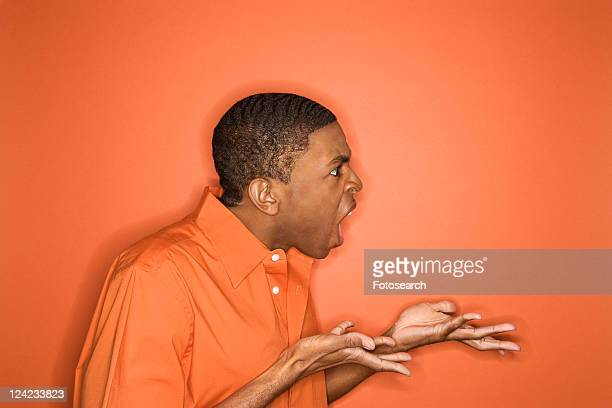 Side view of young African-American man on orange background expressing anger towards unseen person.