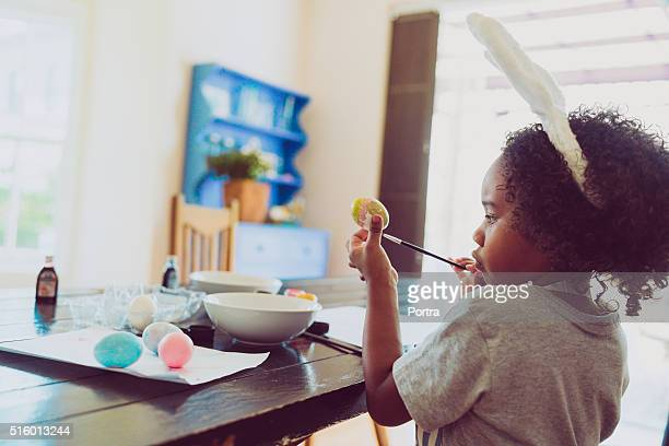 Side view of young boy colouring Easter egg at home