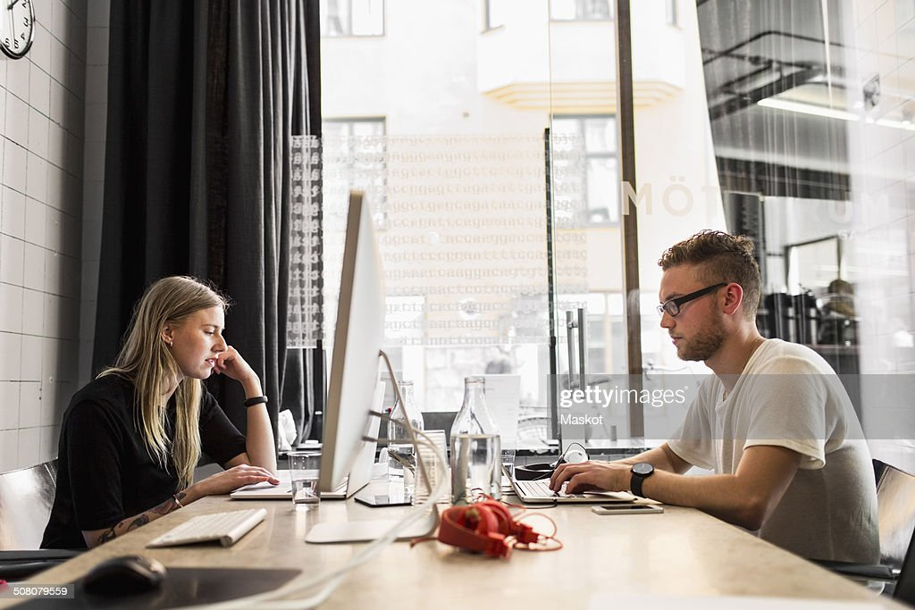 Side view of young businessman and businesswoman working in new office