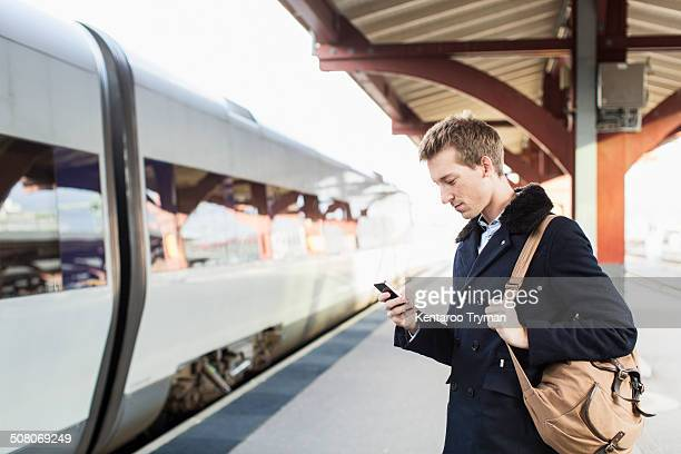 Side view of young businessman using cell phone on railroad station