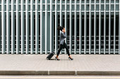 Side view of young businesswoman walking with suitcase