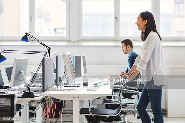 Side view of young businesswoman with colleague working in background at office