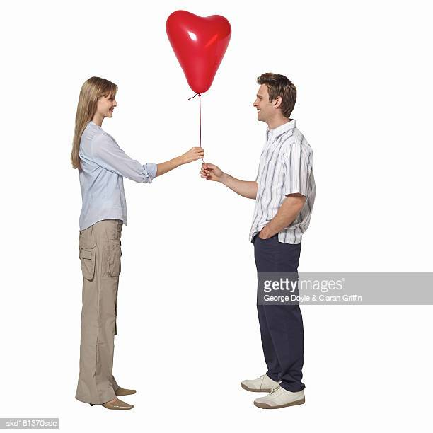 Side view of young couple holding heart shape balloon