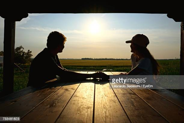 Side View Of Young Couple Sitting On Landscape Against Sunset Sky