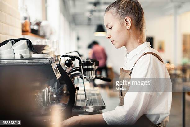 Side view of young female barista using espresso maker at cafe