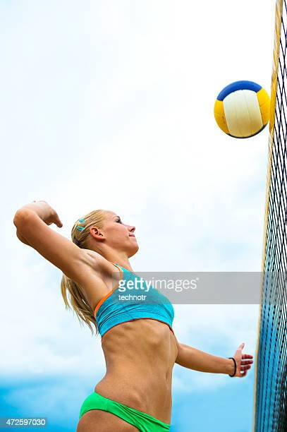 Vista lateral del joven atractiva mujer jugador de vóleibol de acción