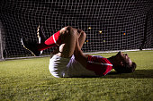 Side view of young male soccer player suffering from knee pain lying down on playing field