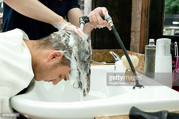 Side view of young man bending forward having hair washed in barbershop