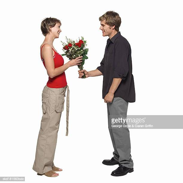 Side view of young man giving young woman bouquet of roses