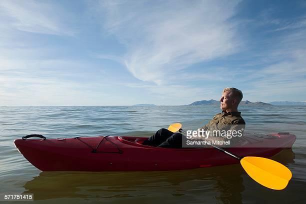Side view of young man in kayak on water holding paddles, eyes closed, Great Salt Lake, Utah, USA