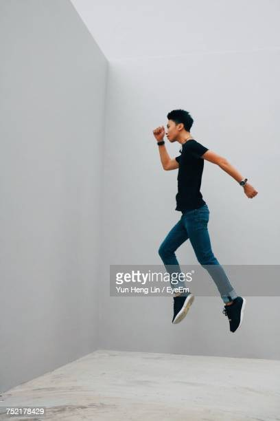 Side View Of Young Man Jumping Against White Wall