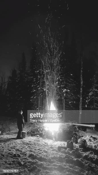 Side View Of Young Man Looking At Bonfire While Standing On Field At Night