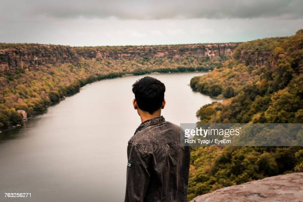 Side View Of Young Man Looking At View While Standing On Mountain Over River Against Cloudy Sky