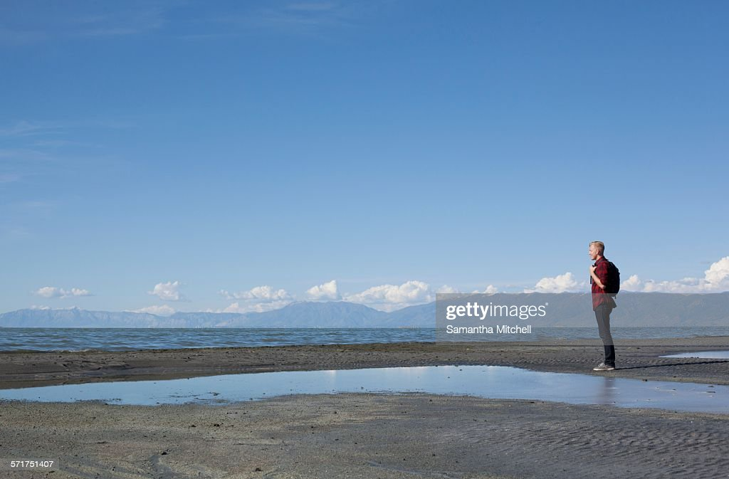Side view of young man standing at waters edge looking out, Great Salt lake, Utah, USA