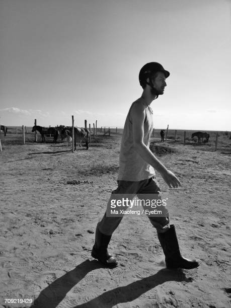 Side View Of Young Man Walking At Farm With Horses In Background