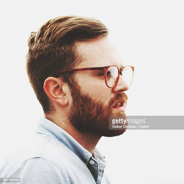 Side View Of Young Man With Beard And Eyeglasses Standing Against White Background