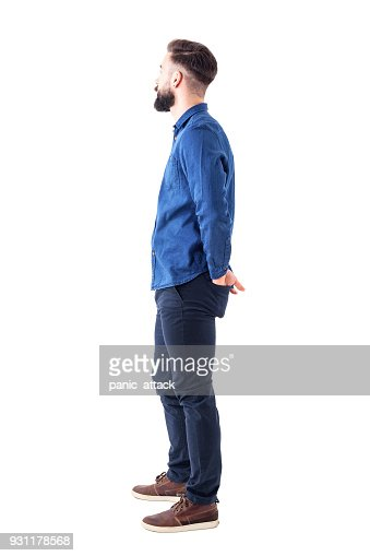 Side view of young stylish bearded man with hands in back pockets standing and watching : Stock Photo