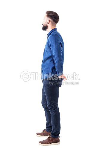 Side view of young stylish bearded man with hands in back pockets standing and watching : Foto de stock