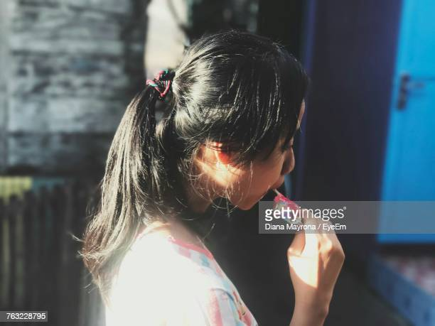 Side View Of Young Woman Eating Sweet Food While Standing Outdoors