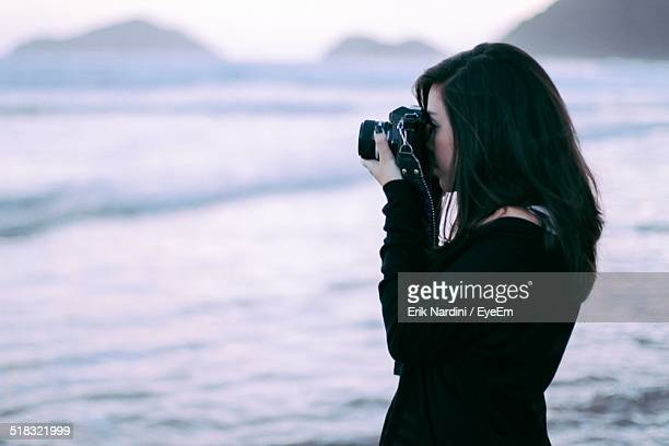 Side View Of Young Woman Photographing At Beach