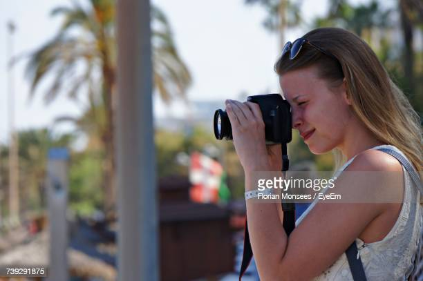 Side View Of Young Woman Photographing Through Camera
