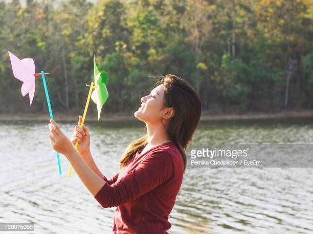 Side View Of Young Woman Playing With Pinwheel By Lake Against Trees